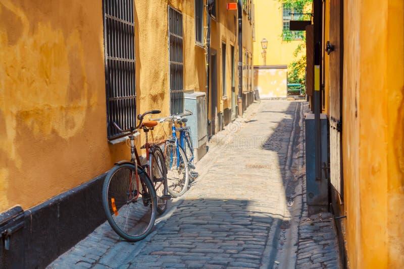 有斯德哥尔摩的Gamla斯坦历史的老中心自行车和黄色中世纪房子的狭窄的鹅卵石街道在夏天 免版税库存照片