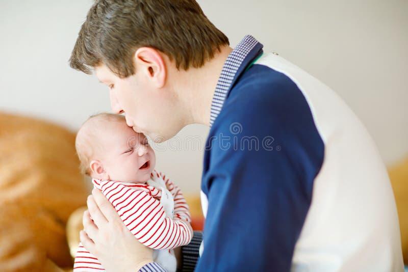 有新出生的小女儿的,家庭画象愉快的骄傲的年轻父亲一起 免版税库存图片