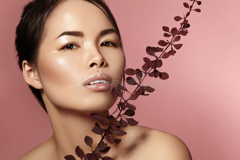 有新每日构成的美丽的亚裔妇女 温泉治疗的越南秀丽女孩与绿色在面孔附近生叶 免版税库存图片