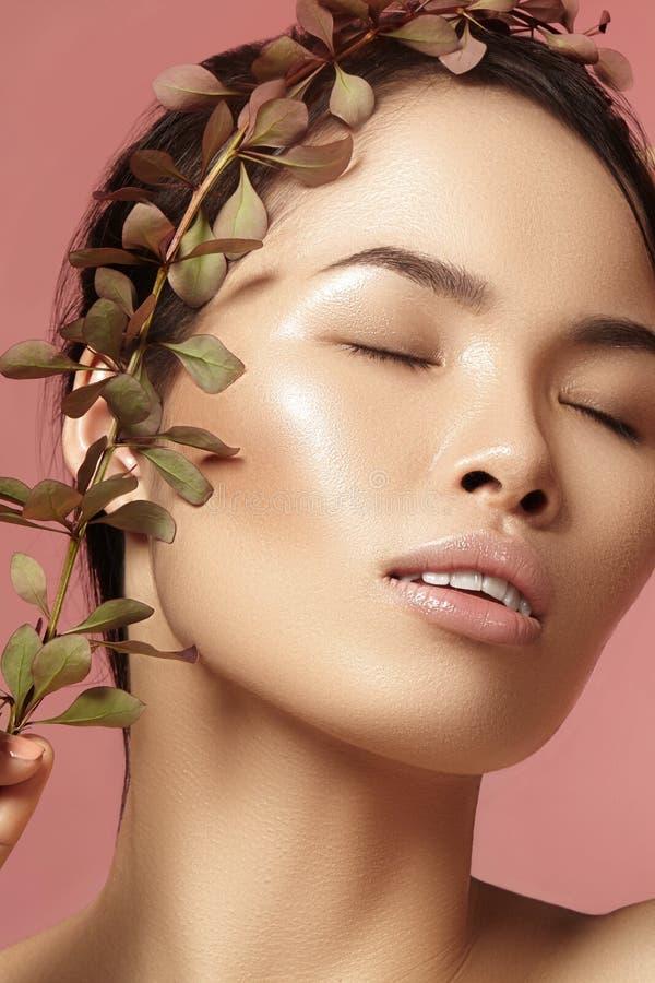 有新每日构成的美丽的亚裔妇女 温泉治疗的越南秀丽女孩与绿色在面孔附近生叶 免版税库存照片