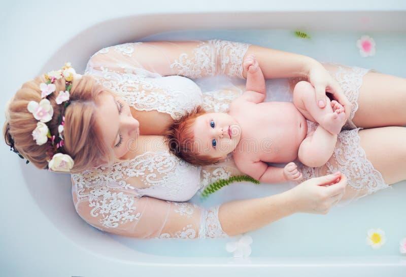 有新生儿女孩的年轻愉快的母亲,花卉牛奶浴的女儿 库存照片
