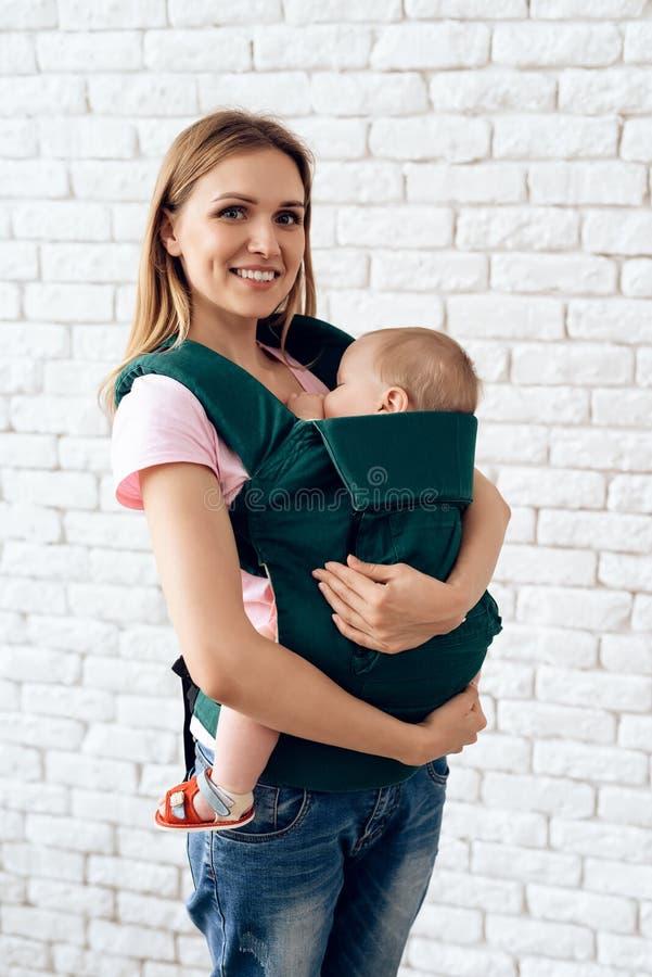 有新生儿的微笑的母亲婴孩吊索的 库存照片