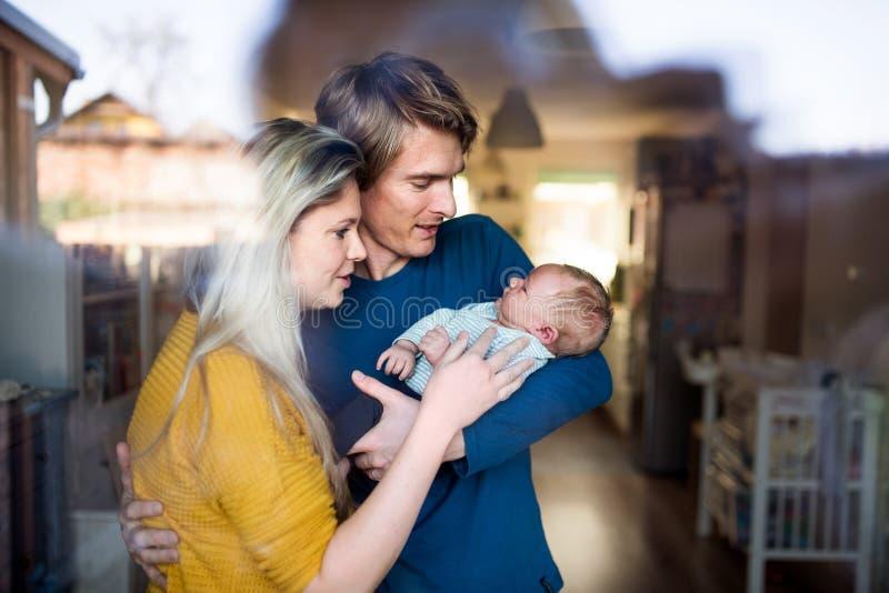 有新生儿的美好的年轻父母在家 射击通过玻璃 免版税库存照片