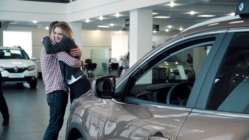 有新的汽车的人惊奇的妇女在展示屋子里 免版税库存照片