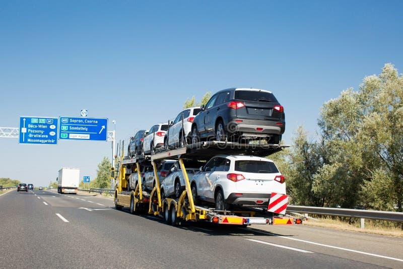 有新的汽车的汽车运载船拖车在床铺平台的待售 汽车在高速公路的运输卡车 免版税图库摄影