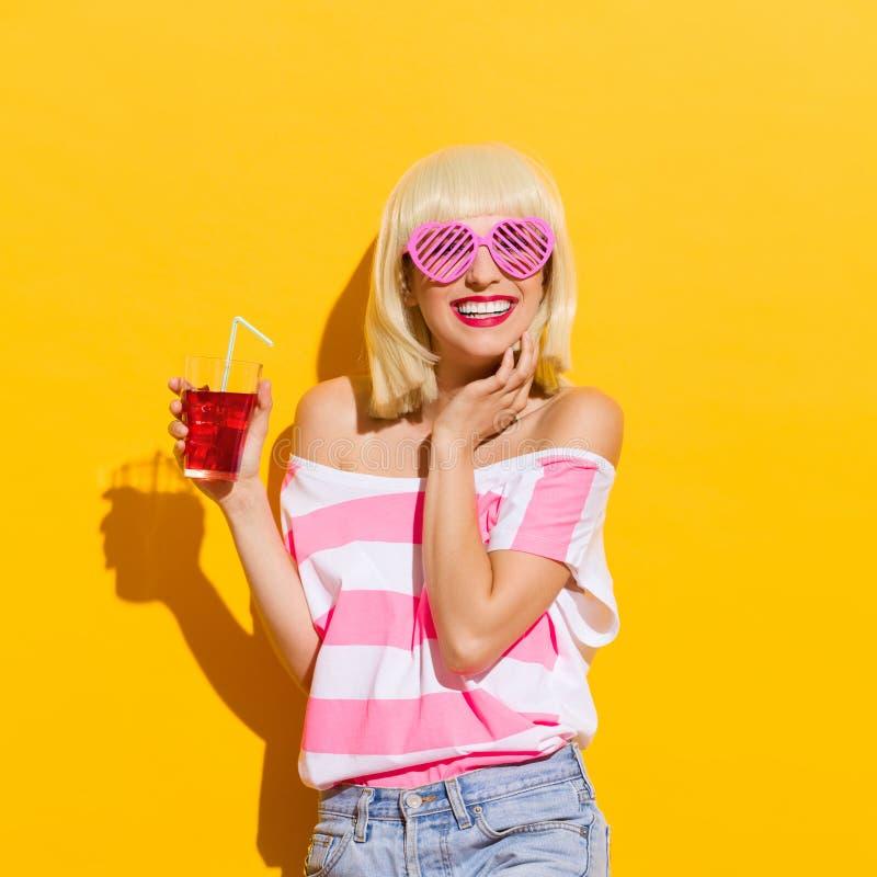 有新红色饮料的微笑的少妇 免版税库存照片