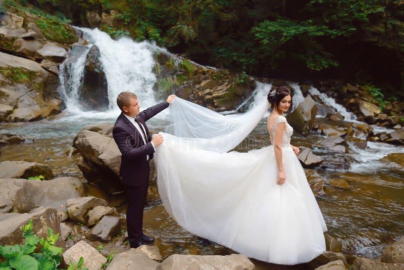 有新郎的愉快的新娘在山瀑布附近 豪华婚礼礼服 成功生活 室外婚姻的夫妇 免版税图库摄影