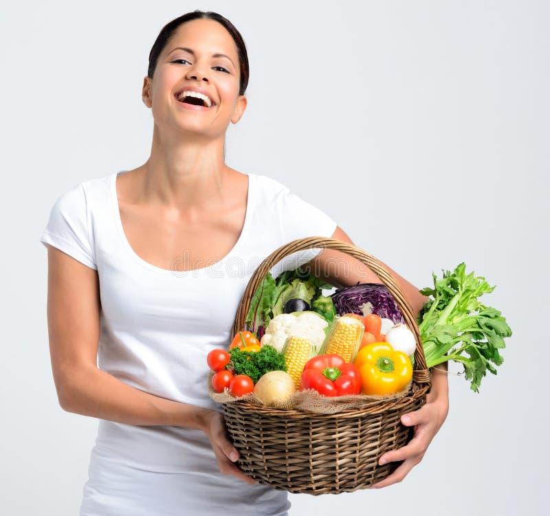 有新鲜农产品的微笑的妇女 库存图片