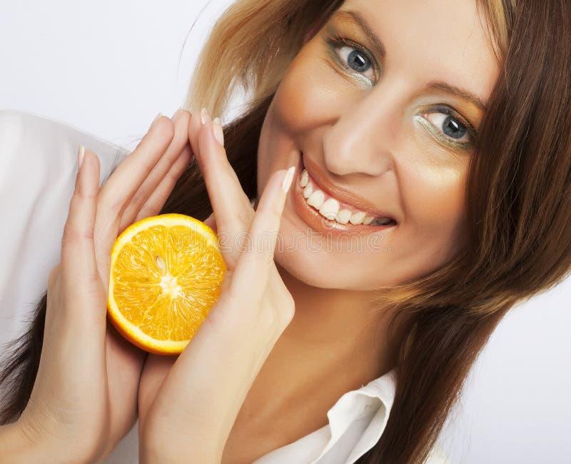 有新鲜橙色近的快乐的妇女她的面孔 免版税库存图片