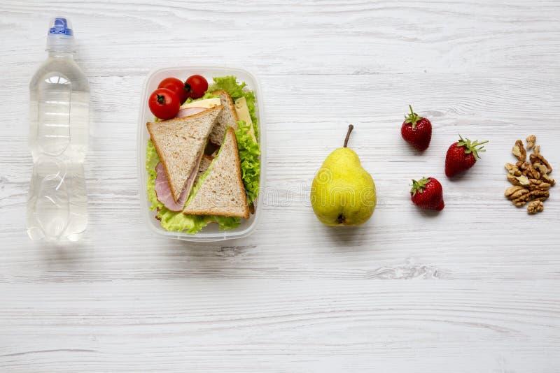 有新鲜的有机菜的三明治、核桃、果子和瓶健康学校午餐箱子在白色木背景, f的水 库存图片