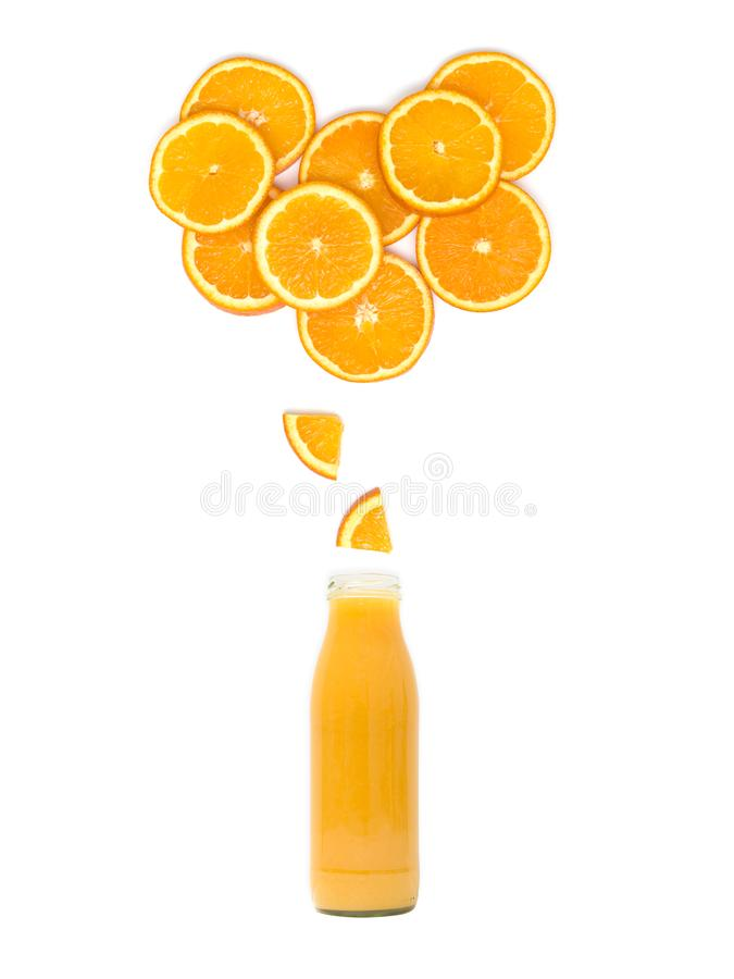 有新鲜的橙汁过去的瓶站立在白色背景的许多橙色切片下 免版税库存图片