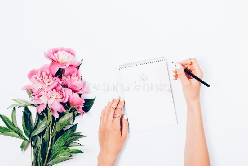 有新鲜的浅粉红色的牡丹花束的风格化女性书桌  免版税库存照片