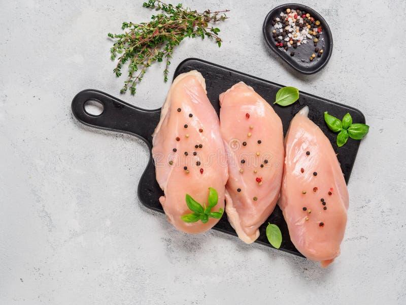 有新鲜的蓬蒿的未加工的在黑cuttingboard, copyspace的鸡胸脯和麝香草 免版税库存照片