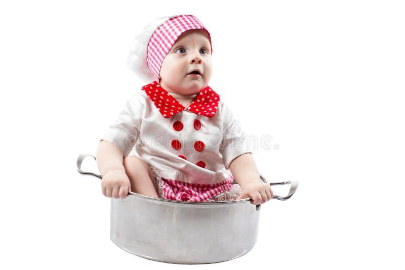 有新鲜蔬菜和果子的小厨师男孩佩带的厨师帽子 免版税库存照片
