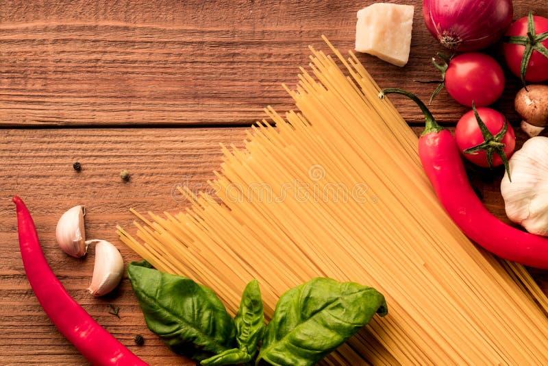 有新鲜蔬菜和香料的-在木背景的顶视图意大利面团意粉 免版税库存照片