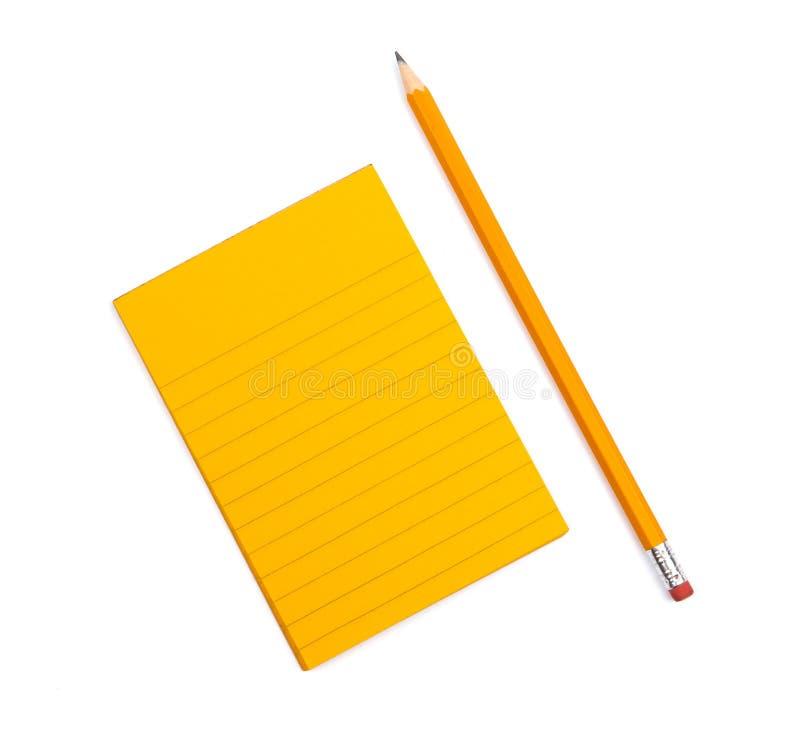 有旁边说谎在白色背景的一支被削尖的铅笔的橙色板料的一个镶边笔记本在 嘲笑与文本的拷贝空间 免版税库存照片