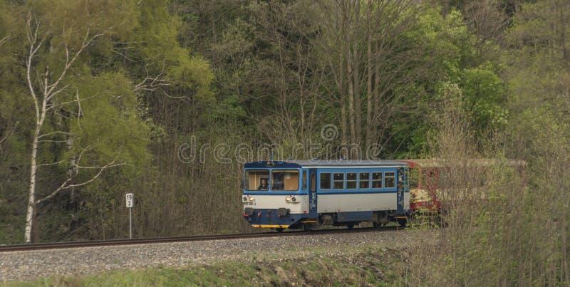 有旅客长途汽车的蓝色和红色柴油火车在Jeseniky山 免版税图库摄影