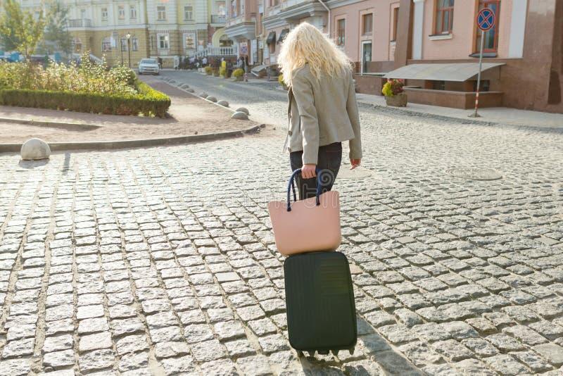 有旅行包和电话的年轻微笑的白肤金发的妇女走在城市街道的,女性与有长的卷发的,看法太阳镜 免版税图库摄影