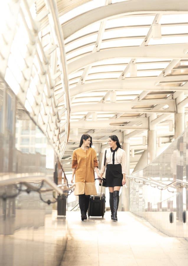 有旅行包的年轻女人走在旅客旅游业的机场的 库存图片