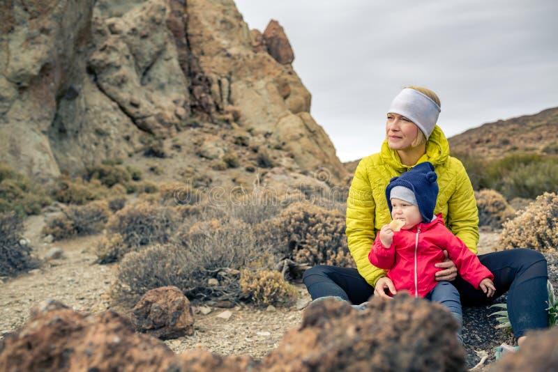 有旅行在山的小男孩的愉快的母亲 库存照片
