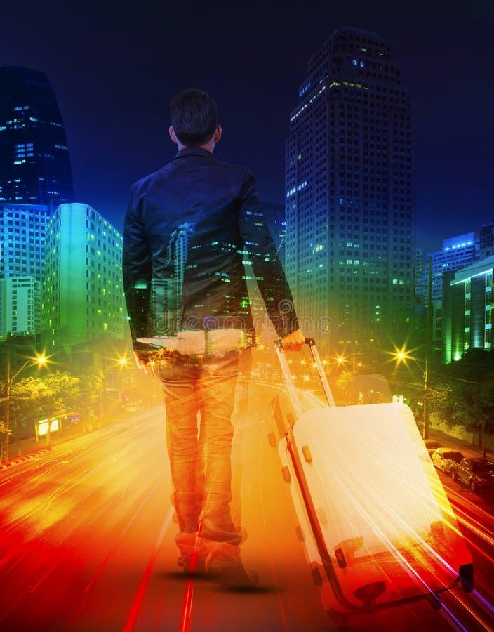 有旅行的行李的年轻人反对照明设备都市scen 免版税库存照片