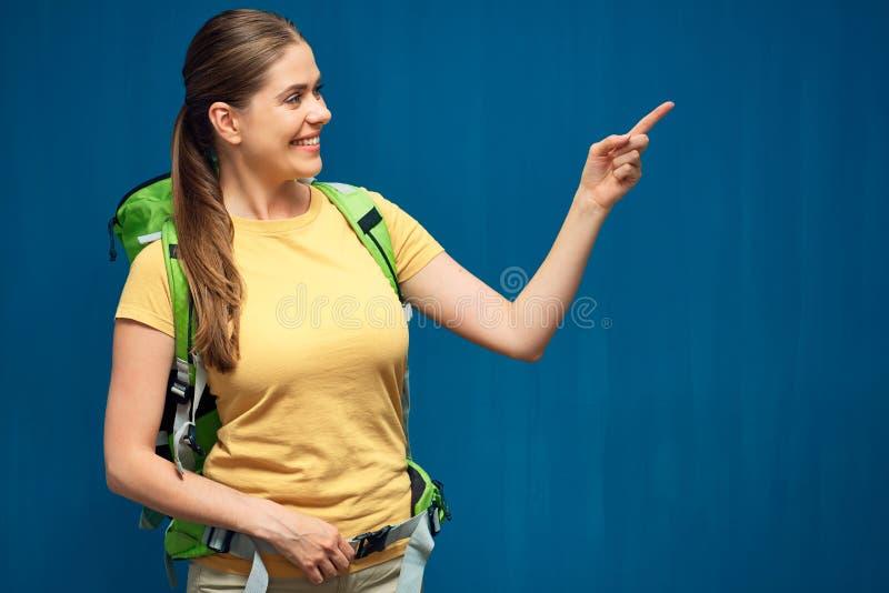 有旅行背包的微笑的妇女指向手指的 库存照片