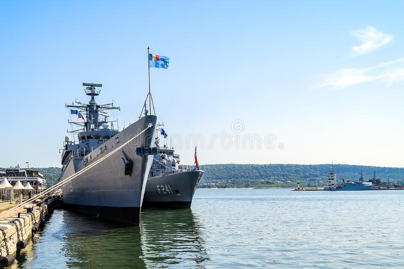 有旗子的两艘大灰色现代军舰被停泊在码头在瓦尔纳海口在一个晴朗的夏日 海军锻炼,攻击 免版税库存图片