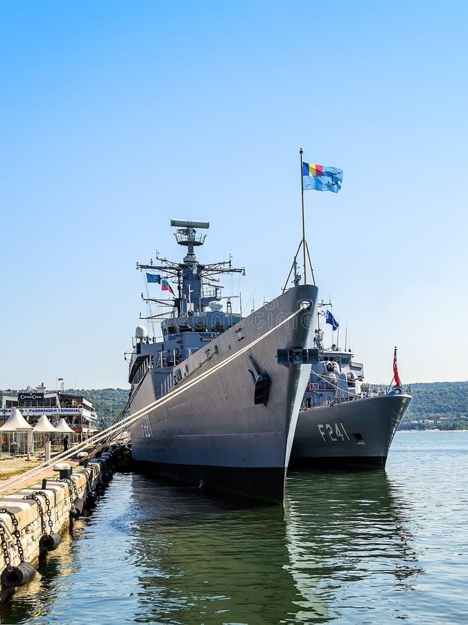 有旗子的两艘大灰色现代军舰被停泊在码头在瓦尔纳海口在一个晴朗的夏日 海军锻炼, 免版税库存照片