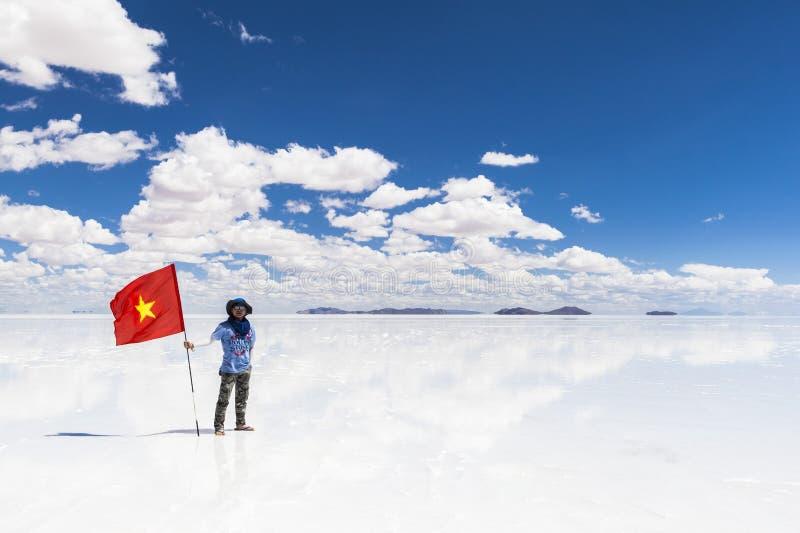 有旗子的人在撒拉族de Uyuni,玻利维亚 库存图片