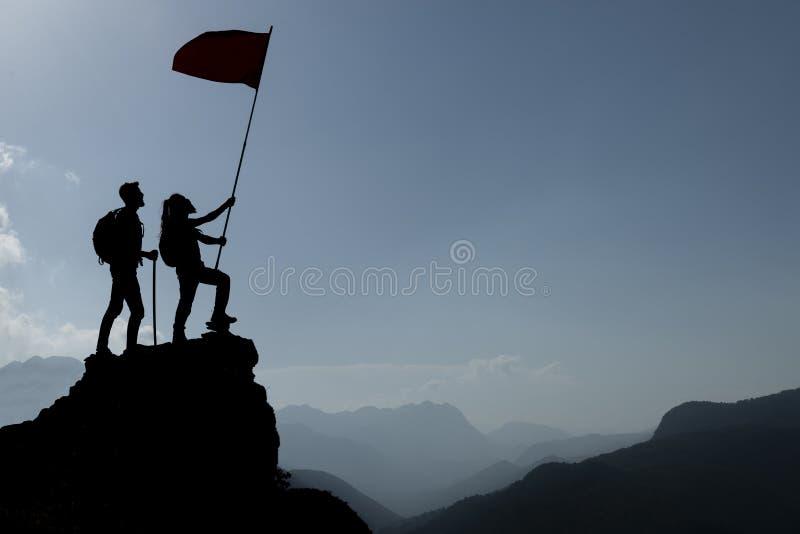 有旗子的剪影登山人在山 免版税库存图片