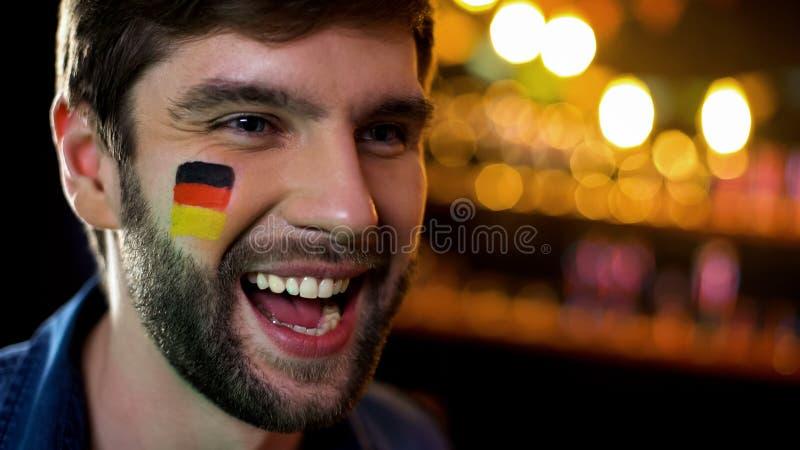 有旗子的快乐的德国爱好者在面颊呼喊和庆祝胜利,目标的 免版税库存照片