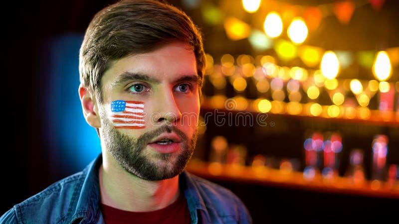 有旗子的急切美国人在面颊观看的竞选,等待的结果 库存图片