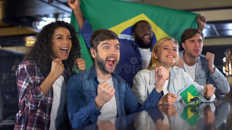 有旗子的情感巴西足球迷庆祝国家队胜利的 免版税图库摄影