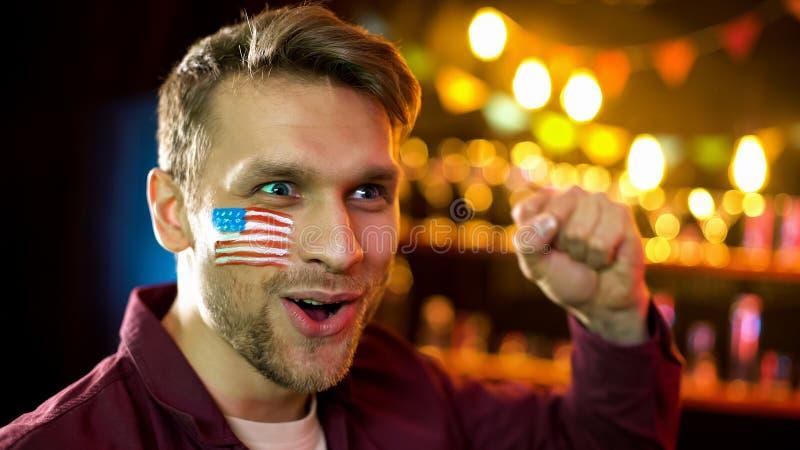 有旗子的情感美式足球爱好者在是做姿态,胜利的面颊 图库摄影
