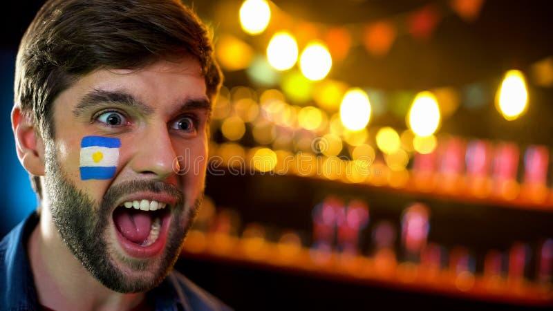 有旗子的情感阿根廷足球迷在面颊庆祝队胜利的 免版税库存照片