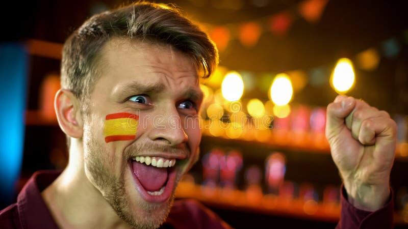 有旗子的愉快的西班牙橄榄球支持者在呼喊的面颊,队计分的目标 图库摄影