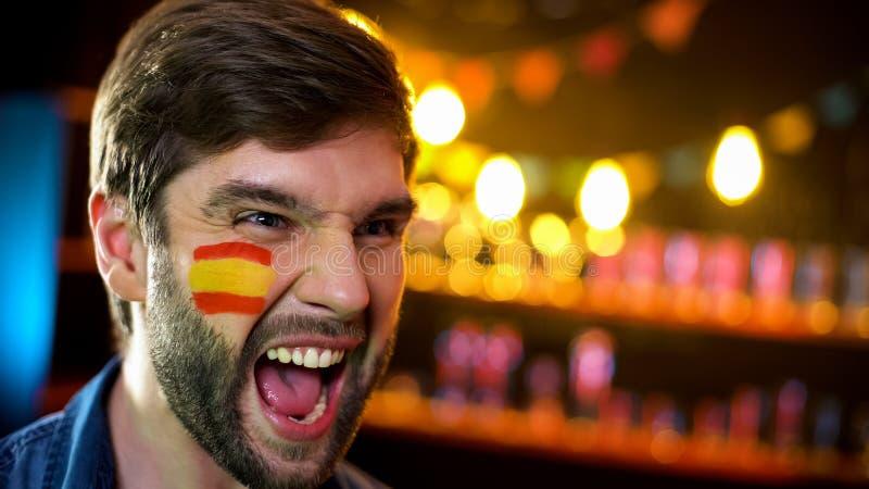 有旗子的西班牙足球迷在面颊欢呼为队赢得的比赛的 库存图片