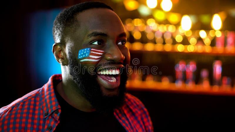 有旗子的非裔美国人的足球迷在面颊欢呼为队赢得的比赛的 库存照片