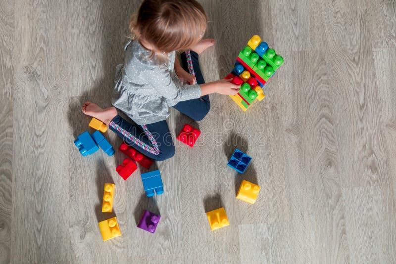 有无法认出的儿童的女孩明亮的塑料建筑块乐趣和修造  使用在地板上的小孩 背景母牛开发的玩具白色 库存照片
