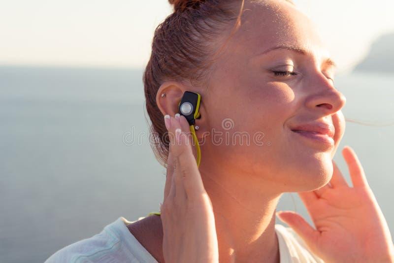有无线耳机的健身女孩 免版税库存图片