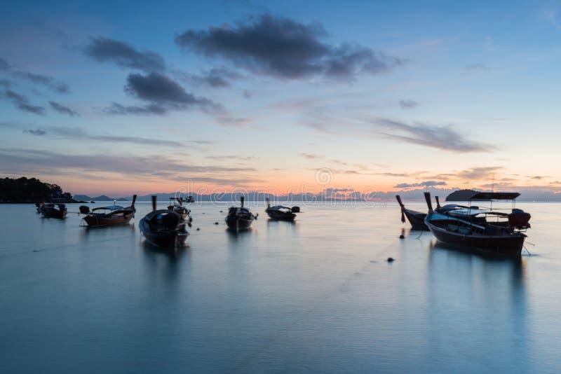 有日出天空的长的曝光剪影长尾巴小船在酸值Lipe海岛 库存照片