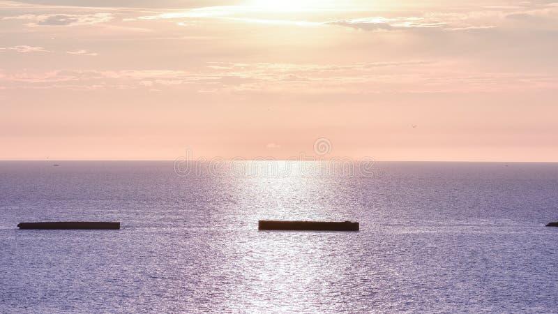 有日落天空的风平浪静 在水和大西洋墙壁的五颜六色的天际 E 库存图片