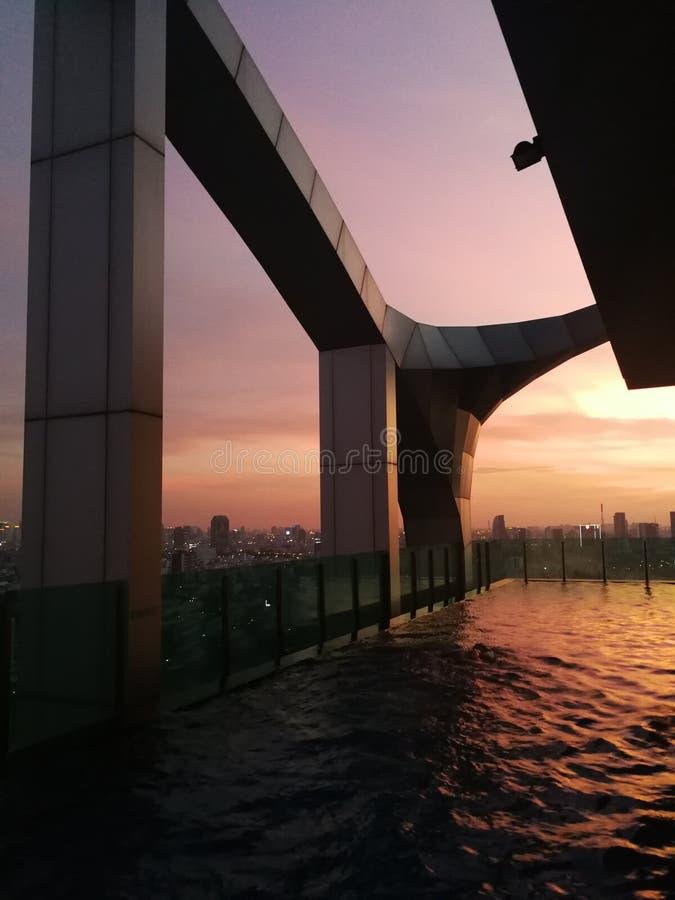 有日落的无限游泳场在曼谷 免版税图库摄影