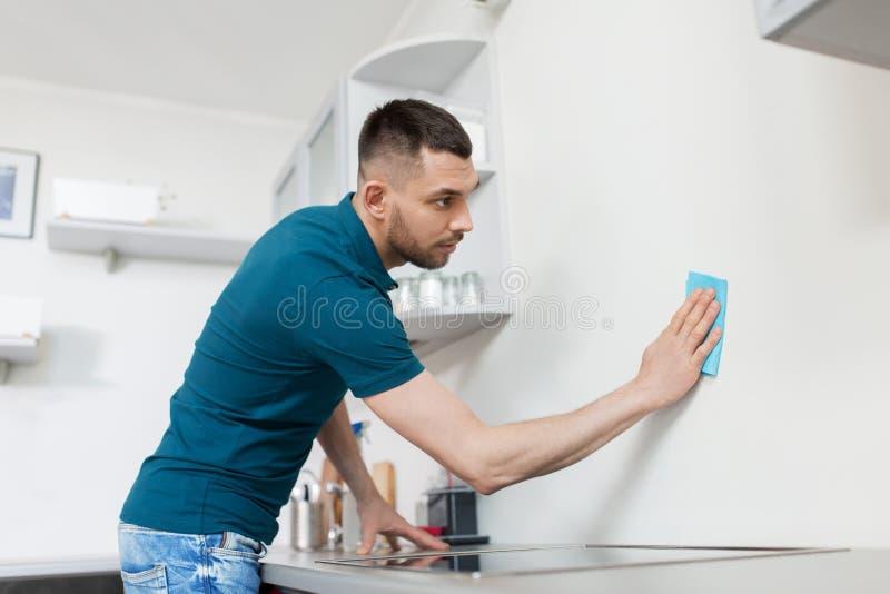 有旧布清洁墙壁在家厨房的人 免版税库存图片