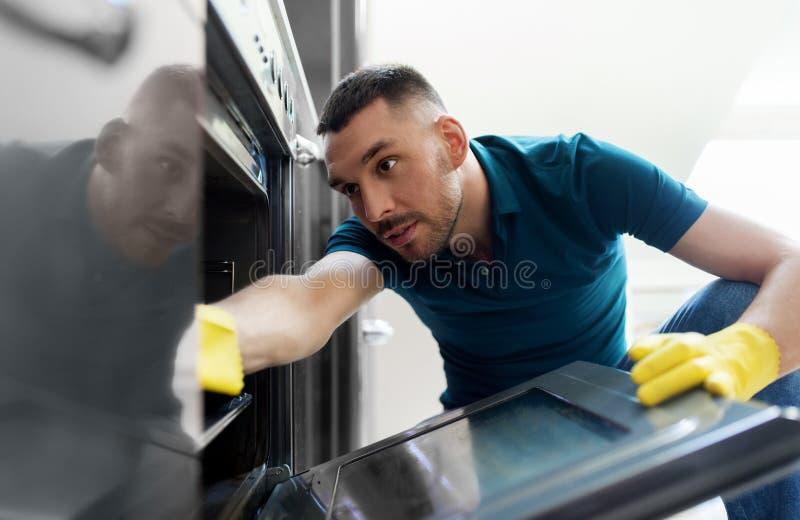 有旧布清洁的人在烤箱在家厨房里面 库存照片