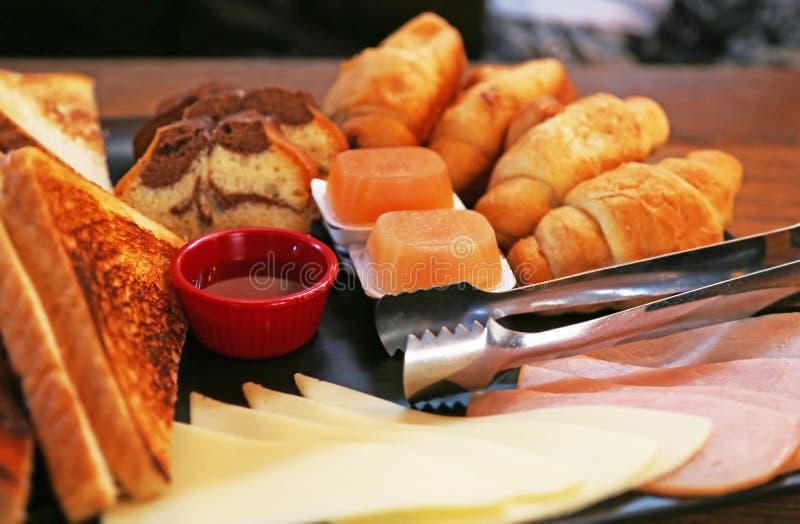 有早午餐的-在木桌上的早餐大板材用多士、蛋糕、新月形面包、蜂蜜、橘子果酱、乳酪和火腿 免版税图库摄影