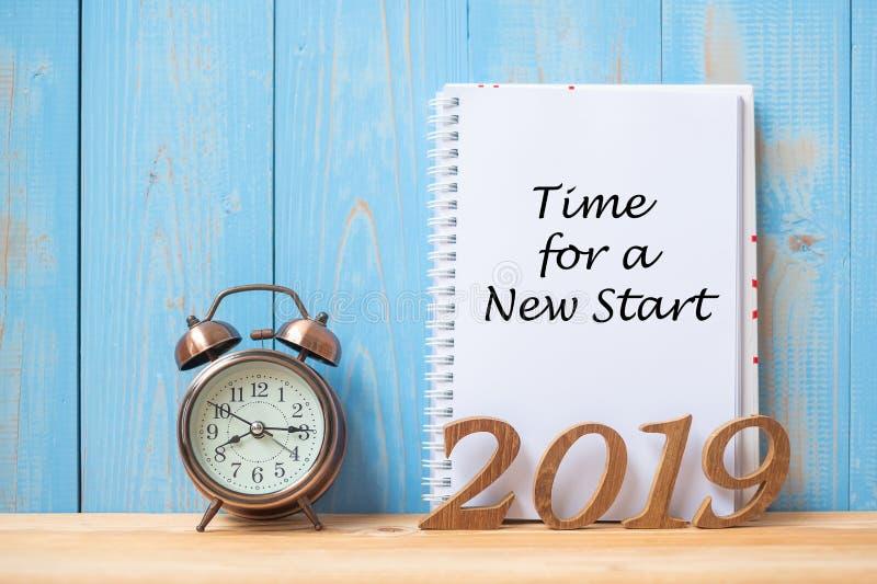 有时刻的2019新年快乐的在笔记本、减速火箭的闹钟和木数字的新的起动文本在桌和拷贝空间上 库存图片