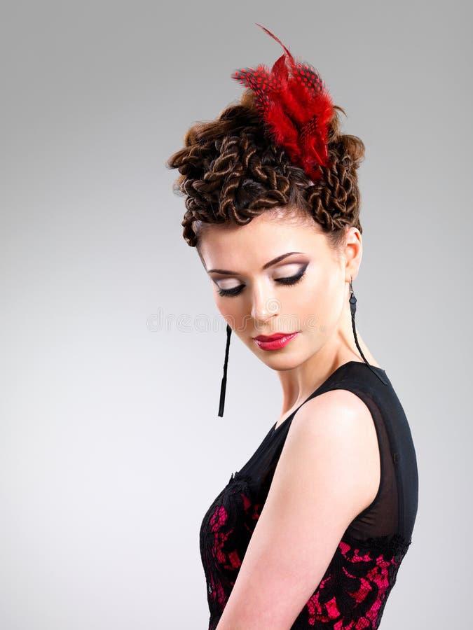 有时尚发型的妇女与在头发的红色羽毛 免版税库存图片