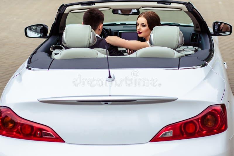有时尚构成和发型的华美的新娘在与英俊的新郎的豪华婚礼礼服在白色敞蓬车汽车附近 库存图片