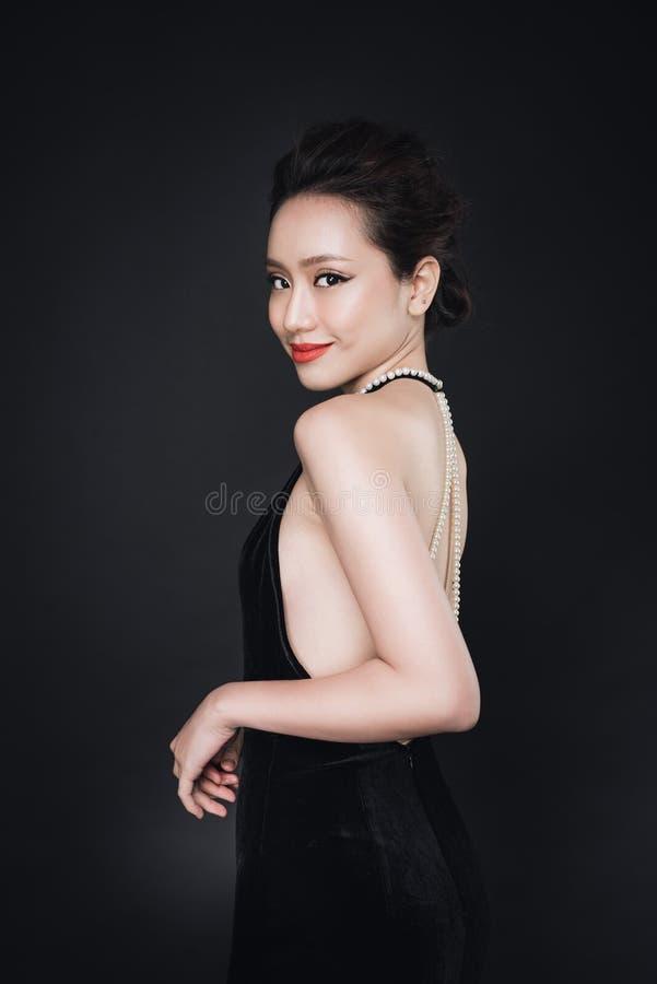 有时尚构成的亚裔妇女在豪华黑礼服 图库摄影